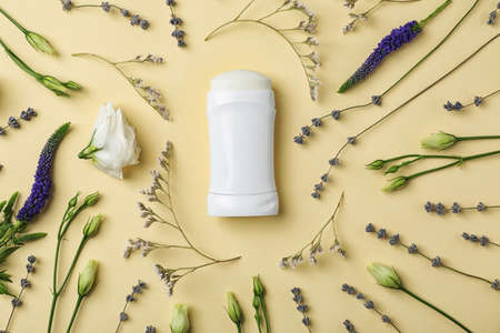 Flat lay composition with deodorant and herbs on color background