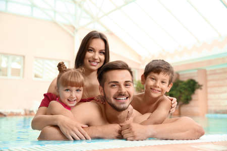 Happy family resting in indoor swimming pool