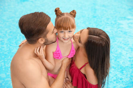 Parents kissing their daughter in swimming pool