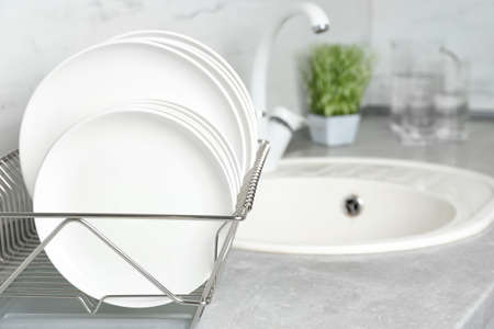 Different clean plates in dish drying rack on kitchen counter Stock Photo