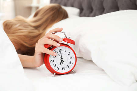 Woman turning off alarm clock in bedroom