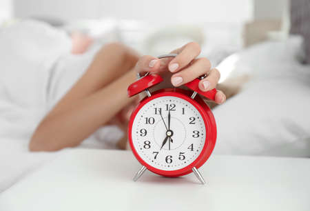 Woman turning off alarm clock in bedroom