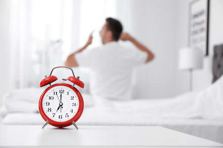 Analog alarm clock and blurred man on background. Time of day Banco de Imagens