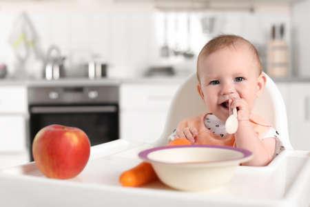 Adorabile bambino fare colazione nel seggiolone al chiuso. Alimenti per bambini sani