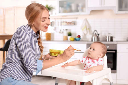 Woman feeding her child in highchair indoors. Healthy baby food