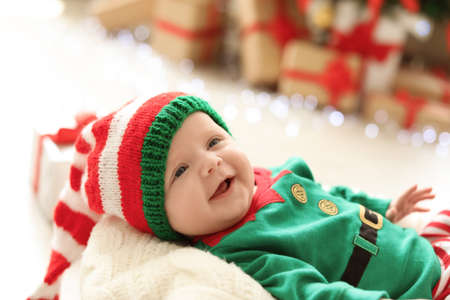 Cute baby in Christmas costume at home