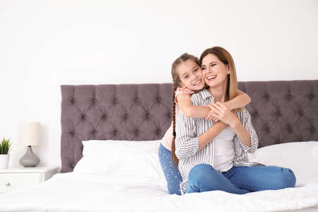 Mother with cute child in bedroom. Happy family