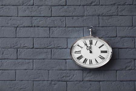 Modern clock on brick wall. Time concept 스톡 콘텐츠