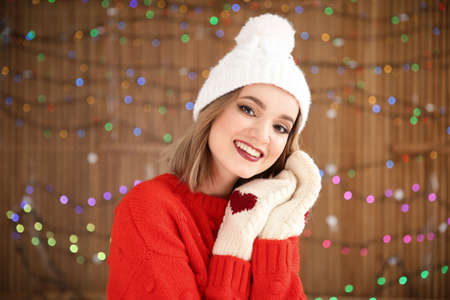 Beautiful young woman in warm clothes posing on blurred lights background. Christmas celebration