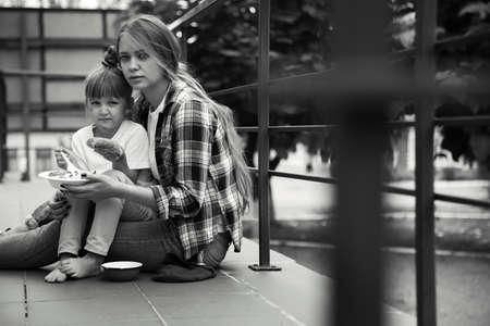 Arme mensen die gedoneerd voedsel eten op straat, zwart-wit effect Stockfoto