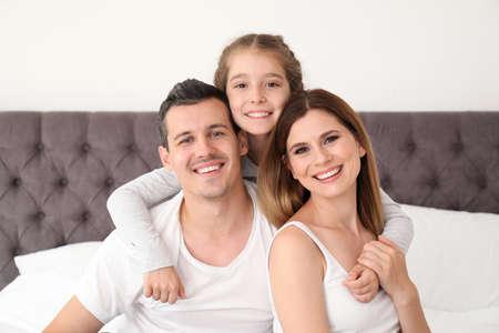 Glückliche Familie mit niedlichem Kind im Schlafzimmer