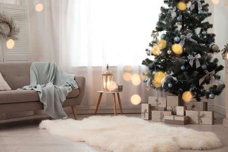 Stilvolles Wohnzimmerinterieur mit geschmücktem Weihnachtsbaum und verschwommenen Lichtern im Vordergrund Standard-Bild