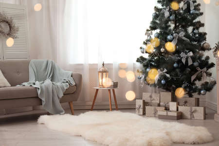 Stylish living room interior with decorated Christmas tree and blurred lights in foreground