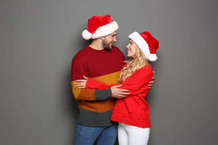 Young couple in Santa hats on grey background. Christmas celebration