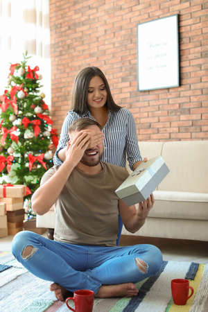 Young woman surprising her boyfriend with Christmas gift at home