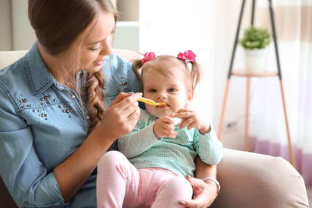 Caring mother feeding her cute little baby with healthy food at home