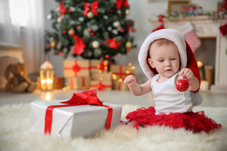 Cute baby in Santa hat playing with jingle bell at home. Christmas celebration Stock Photo