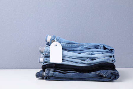 Stack of stylish jeans with tag on table Stock Photo