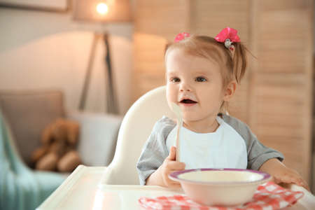 Cute little girl eating healthy food at home