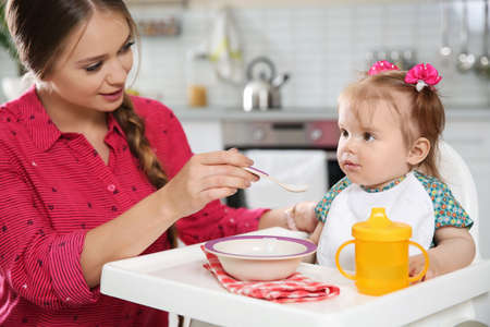 Mother feeding her little baby with healthy food in kitchen