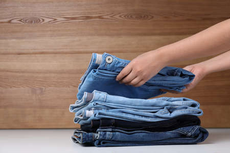 Young woman folding stylish jeans on table