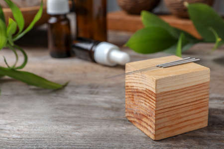 Wooden cube with needles for acupuncture on table Stock Photo