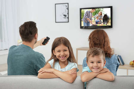 Family watching TV on sofa at home Stock Photo