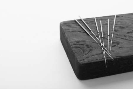 Board with needles for acupuncture on white background Stock Photo