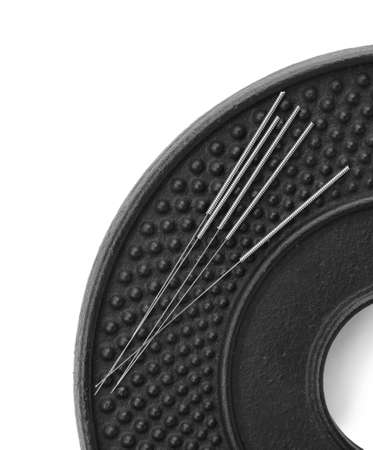 Plate with acupuncture needles on white background