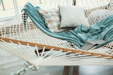 Comfortable hammock with plaid and pillows in living room