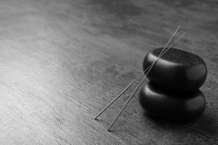 Acupuncture needles and stones on dark table Stock Photo