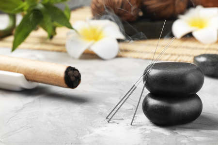 Needles for acupuncture and stones on table