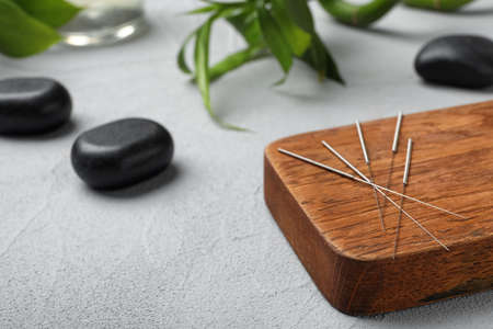Board with needles for acupuncture on table Stock Photo