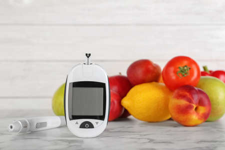 Digital glucometer, fruits and vegetables on table. Diabetes concept Stock Photo