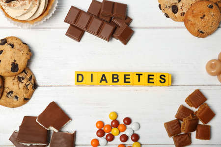 Flat lay composition with word Diabetes and sweets on wooden background