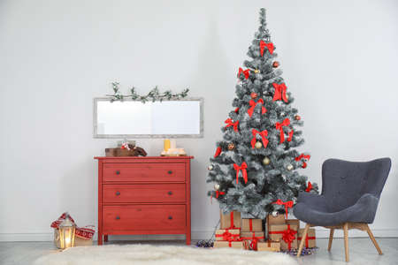 Decorated Christmas tree and armchair in stylish living room interior
