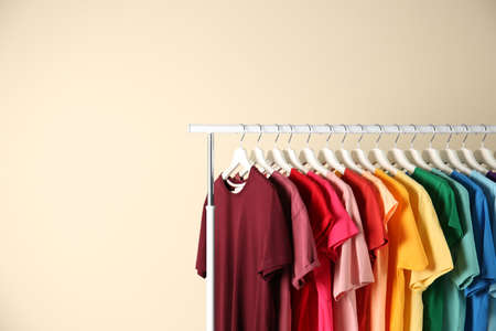 Many t-shirts hanging in order of rainbow colors on light background Standard-Bild