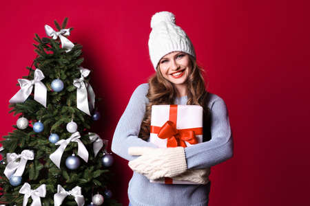 Beautiful young woman in hat and mittens with gift box near Christmas tree on color background