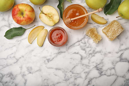 Flat lay composition with honey, apples, dipper and honeycombs on marble background