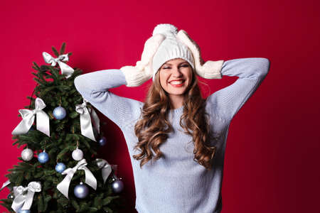 Beautiful young woman in hat and mittens near Christmas tree on color background