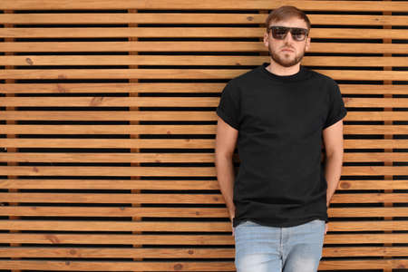 Young man wearing black t-shirt against wooden wall on street. Urban style Imagens