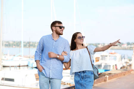 Young hipster couple in jean clothes on pier Foto de archivo