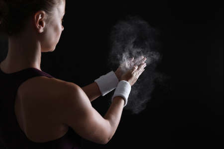 Young woman applying chalk powder on hands against dark background Stock Photo