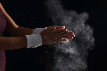 Young woman applying chalk powder on hands against dark background