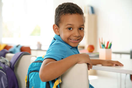 Cute little child sitting at desk in classroom. Elementary school