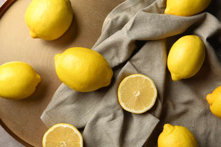 Flat lay composition with lemons, fabric and golden plate, closeup