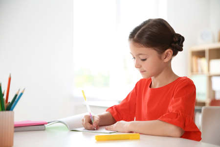 Cute little child doing assignment at desk in classroom. Elementary school