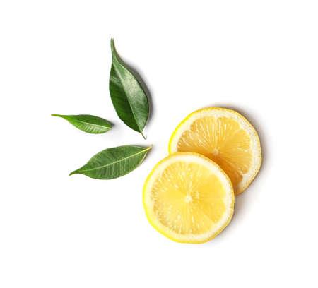 Composición laicos plana con rodajas de limón y hojas sobre fondo blanco. Foto de archivo