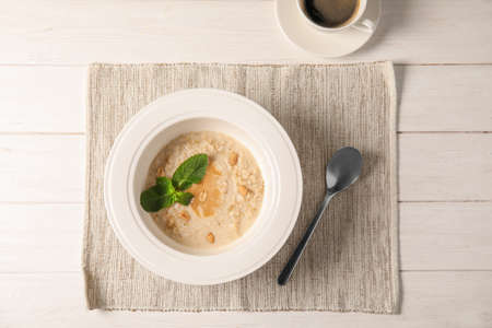 Plate with prepared oatmeal on wooden table, top view