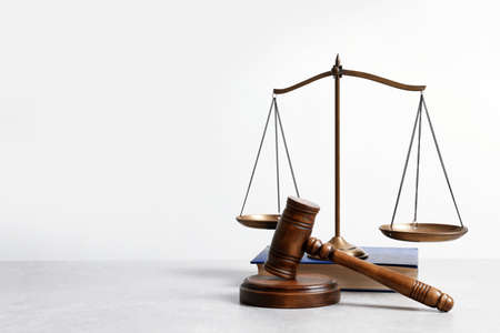 Wooden gavel, scales of justice and book on table. Law concept